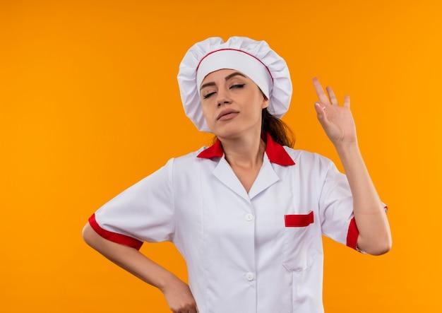コピースペースでオレンジ色の背景に分離されたシェフの制服のジェスチャーで若いイライラする白人料理人の女の子okハンドサイン