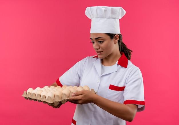 シェフの制服を着た若いイライラする白人料理人の女の子は、コピースペースでピンクの背景に分離された卵のバッチを保持し、見ています