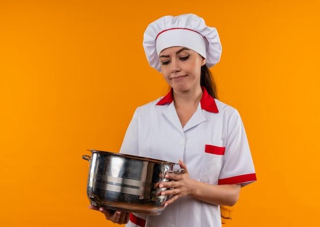 シェフの制服を着た若いイライラする白人料理人の女の子は、コピースペースでオレンジ色の背景に分離された鍋を保持し、見ています