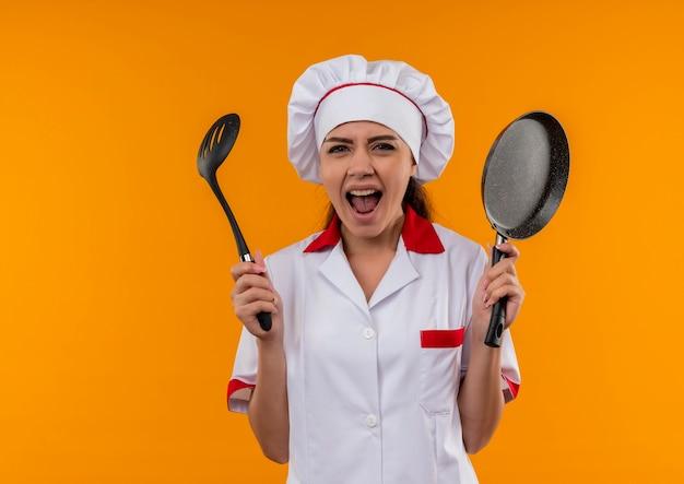 シェフの制服を着た若いイライラする白人料理人の女の子は、コピースペースでオレンジ色の背景に分離されたフライパンとヘラを保持します。