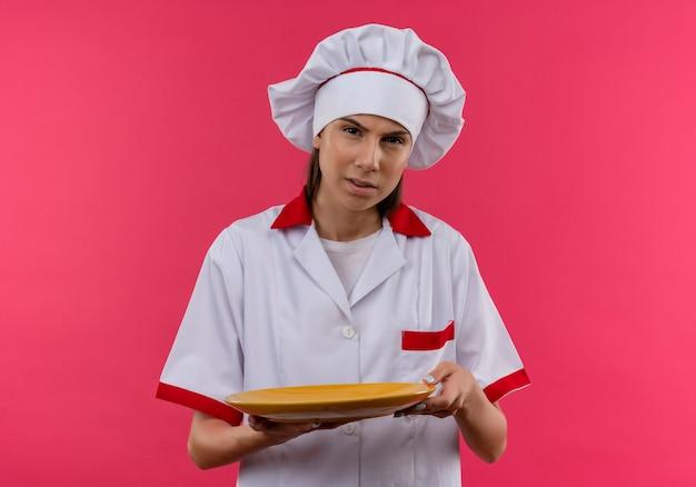 シェフの制服を着た若いイライラする白人料理人の女の子は、コピースペースとピンクのスペースで隔離のプレートを保持します