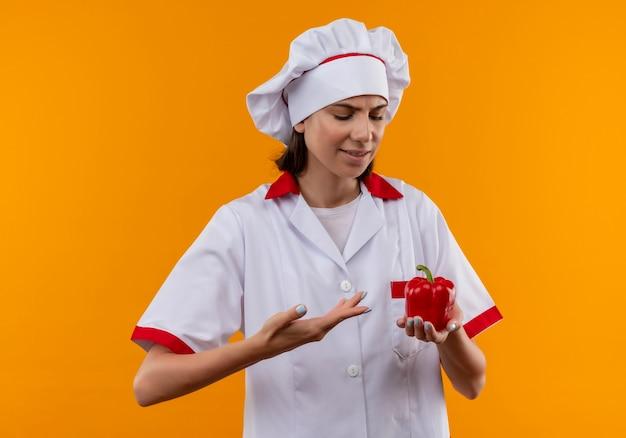 シェフの制服を着た若いイライラする白人料理人の女の子は、コピースペースとオレンジ色のスペースに分離された赤唐辛子を見てポイント