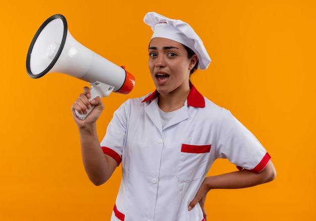シェフの制服を着た若いイライラする白人料理人の女の子は、コピースペースでオレンジ色の背景に分離されたスピーカーを通して話すふりをします