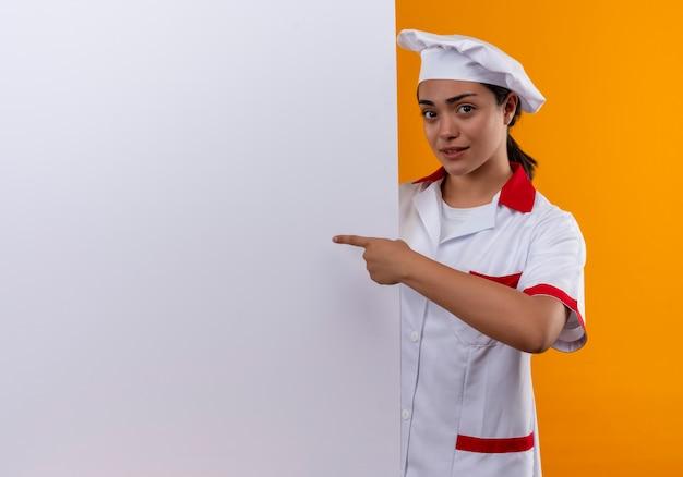 Молодая раздраженная кавказская девушка-повар в униформе шеф-повара стоит за белой стеной и указывает на стену, изолированную на оранжевом фоне с копией пространства