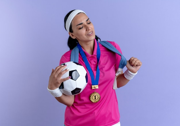 Young annoyed caucasian sporty woman wearing back bag headband and wristbands with gold medal around her neck holds ball isolated on purple space with copy space