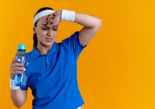 La giovane donna sportiva caucasica infastidita che indossa la fascia e i braccialetti mette la mano sulla testa tiene la bottiglia di acqua che guarda giù sull'arancia con lo spazio della copia