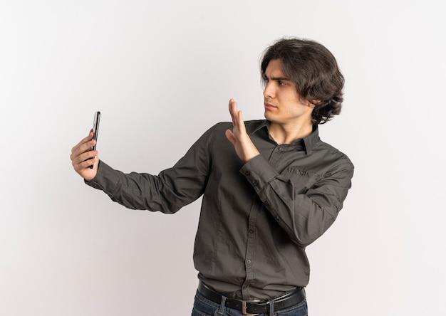 Молодой раздраженный красивый кавказский мужчина держит и смотрит на телефон с поднятой рукой, изолированной на белом фоне с копией пространства
