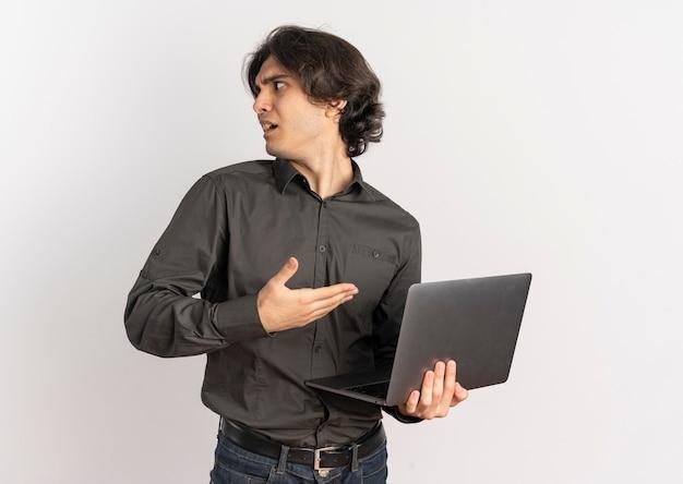 Молодой раздраженный красивый кавказский мужчина держит и указывает на ноутбук, глядя в сторону, изолированную на белом фоне с копией пространства