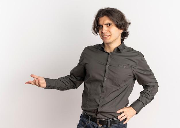 Il giovane uomo caucasico bello infastidito tiene la mano aperta ed esamina la macchina fotografica isolata su fondo bianco con lo spazio della copia