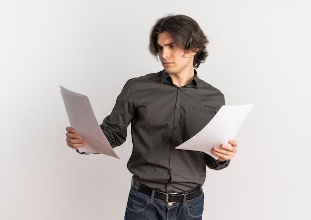 Il giovane uomo caucasico bello infastidito tiene ed esamina i fogli di carta bianca in bianco isolati su fondo bianco con lo spazio della copia