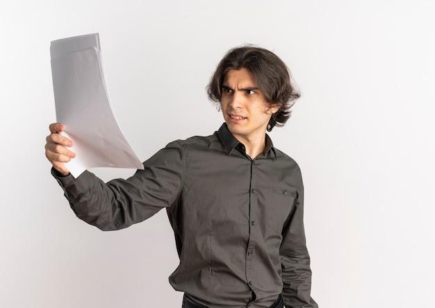 Il giovane uomo caucasico bello infastidito tiene ed esamina i fogli di carta bianca isolati su fondo bianco con lo spazio della copia