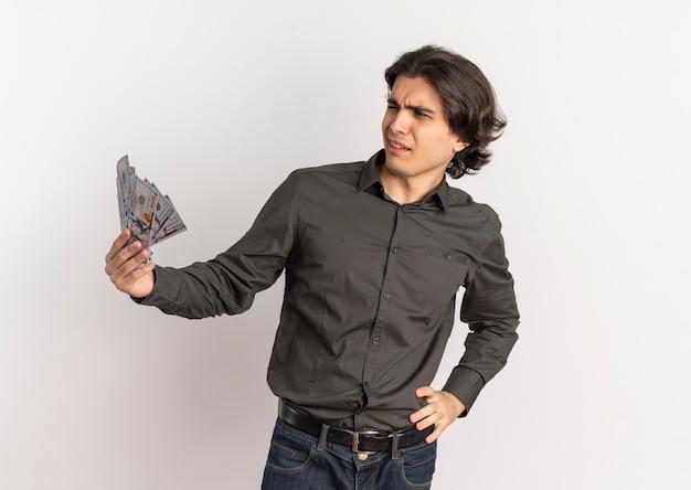 Il giovane uomo caucasico bello infastidito tiene i soldi e guarda al lato isolato su fondo bianco con lo spazio della copia