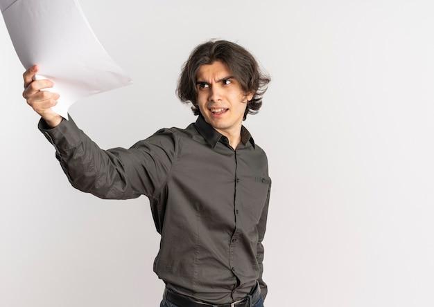 Il giovane uomo caucasico bello infastidito solleva fogli di carta bianca vuota e guarda il lato isolato su sfondo bianco con spazio di copia
