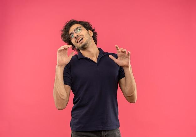 Giovane uomo infastidito in camicia nera con vetri ottici tiene le mani in alto e guarda al lato isolato sulla parete rosa