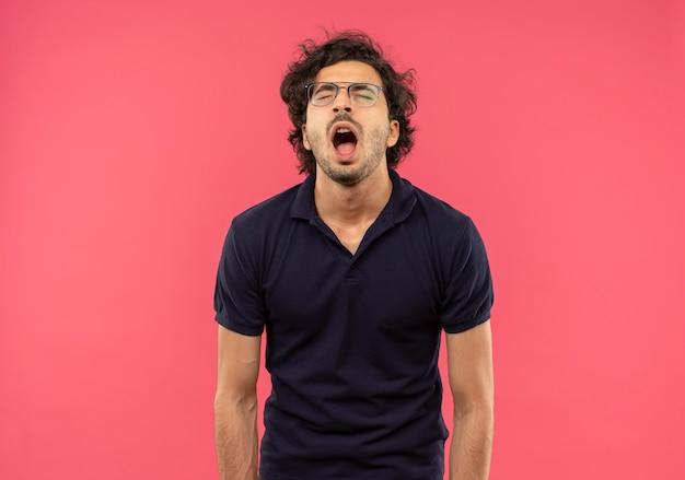 Giovane uomo infastidito in camicia nera con vetri ottici urla con gli occhi chiusi isolati sulla parete rosa