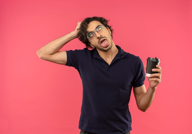 Young annoyed man in black shirt with optical glasses, sticks out tongue and holds coffe cup isolated on pink wall