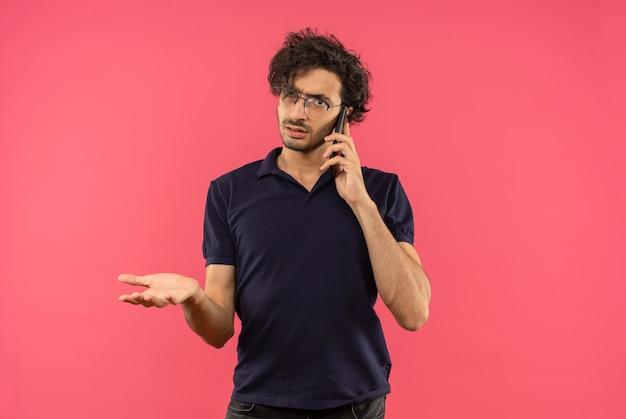 Il giovane uomo infastidito in camicia nera con vetri ottici parla al telefono e tiene la mano aperta isolata sul muro rosa