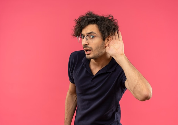 Young annoyed man in black shirt with optical glasses try to hear with hand cupped to ear isolated on pink wall