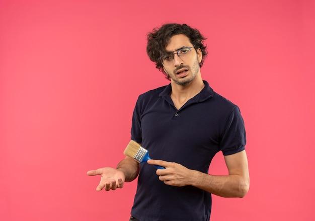Молодой раздраженный мужчина в черной рубашке с оптическими очками держит кисть, изолированную на розовой стене