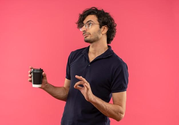 光学メガネと黒いシャツを着た若いイライラした男は、側面を見て、ピンクの壁に隔離されたコーヒーカップを保持