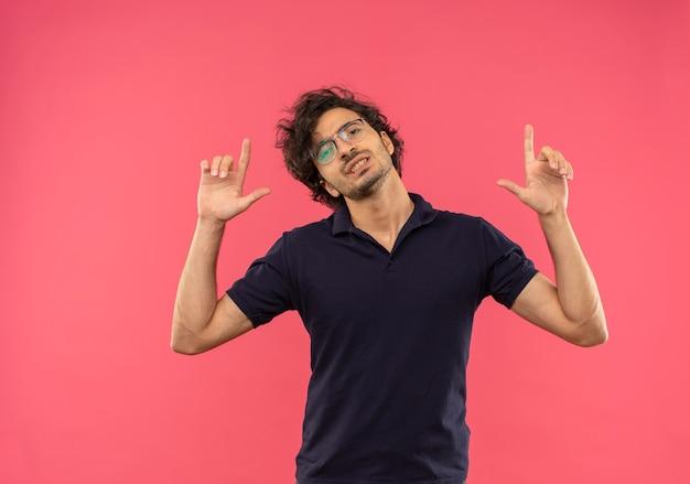 光学メガネと黒いシャツを着た若いイライラした男が上を向いてピンクの壁に孤立して見える