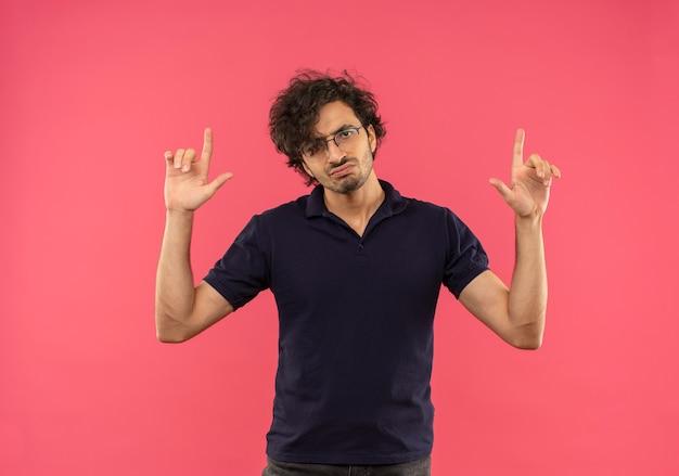 Молодой раздраженный мужчина в черной рубашке с оптическими очками поджимает губы и указывает вверх изолированно на розовой стене