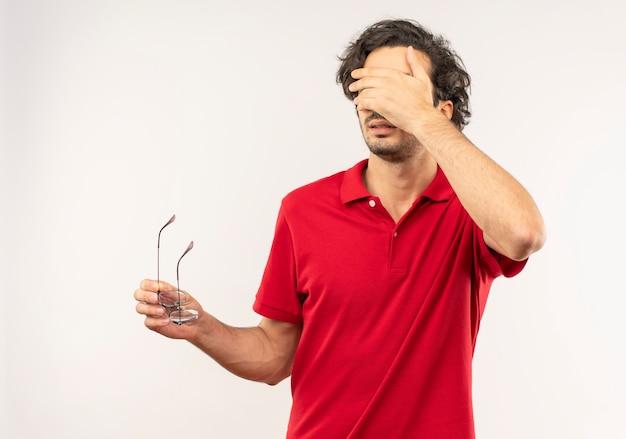 赤いシャツを着た若いイライラした男は、光学メガネを保持し、白い壁で隔離の顔に手を置きます。
