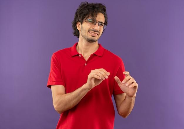 Молодой раздраженный мужчина в красной рубашке с оптическими очками держит руки вверх изолированными на фиолетовой стене