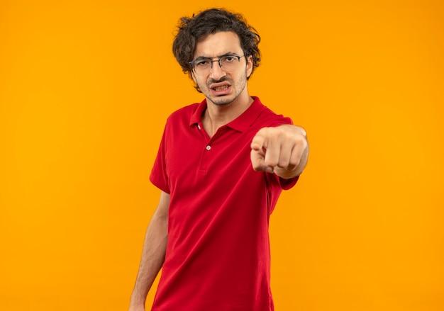 Молодой раздраженный человек в красной рубашке с очками оптических очков, изолированные на оранжевой стене