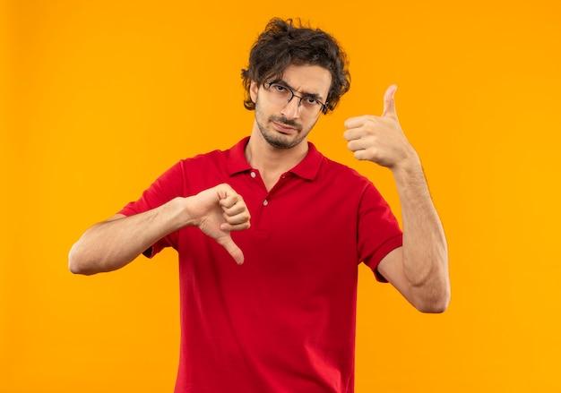 Молодой раздраженный мужчина в красной рубашке с большими пальцами руки вверх и вниз в оптических очках изолирован на оранжевой стене