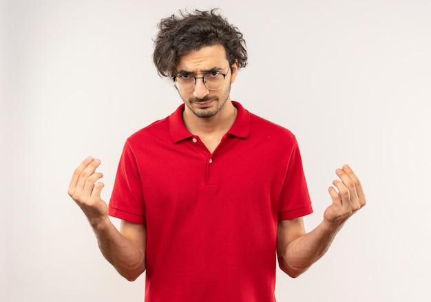 Giovane uomo infastidito in camicia rossa con occhiali ottici gesti il segno della mano dei soldi e sembra isolato sul muro bianco
