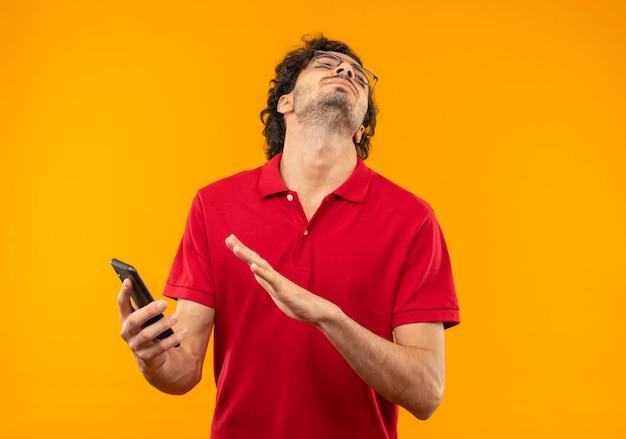 Il giovane uomo infastidito in camicia rossa con vetri ottici tiene il telefono e guarda in alto isolato sulla parete arancione