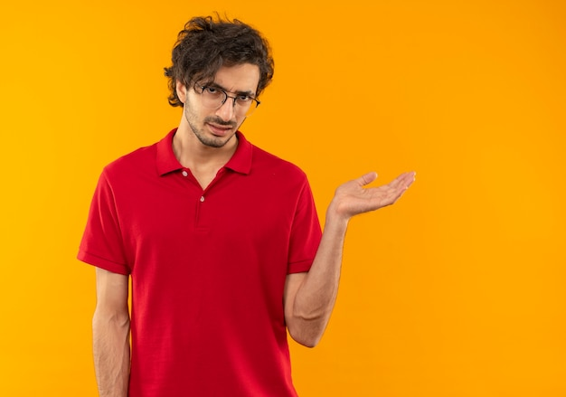Young annoyed man in red shirt with optical glasses points at side with hand isolated on orange wall