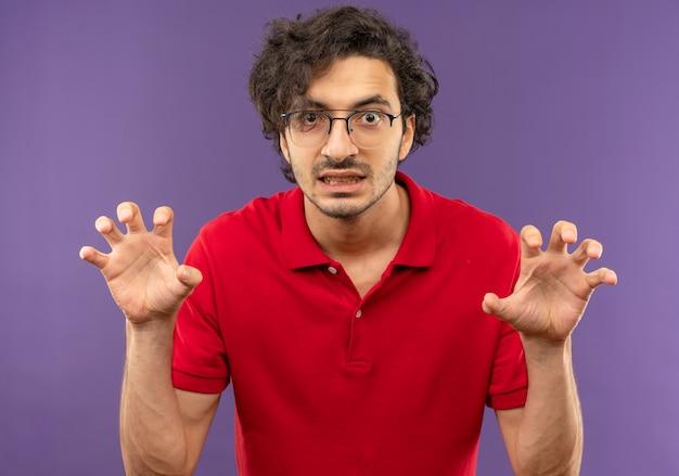 Giovane uomo infastidito in camicia rossa con vetri ottici stringe le dita e finge di attaccare uisolated sulla parete viola