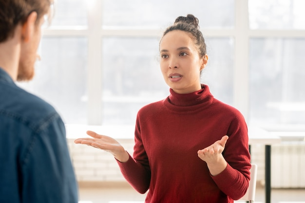 Young annoyed mixed-race woman in maroon pullover explaining her trouble to groupmate of friend