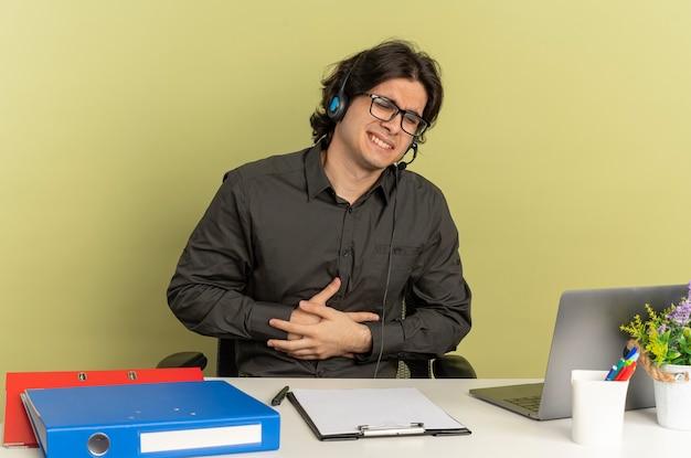 광학 안경에 헤드폰에 젊은 화가 회사원 남자는 복사 공간이 녹색 배경에 고립 된 배꼽에 손을 노트북을 사용하는 사무실 도구와 책상에 앉아
