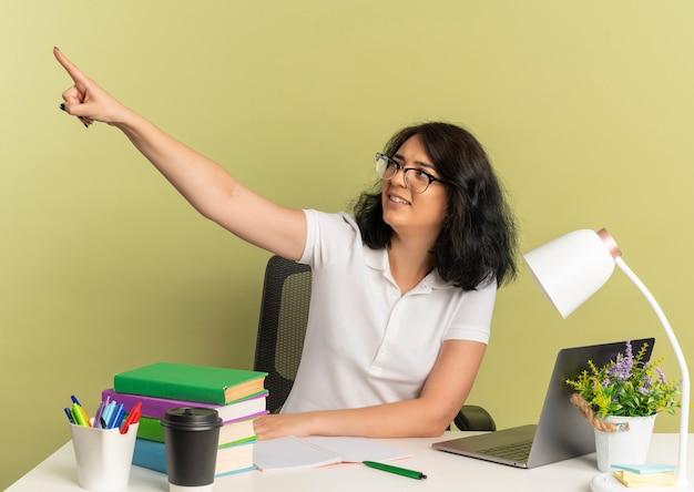 안경을 쓰고 젊은 화가 예쁜 백인 여학생은 학교 도구 외모와 복사본 공간이 녹색 측면에서 포인트와 책상에 앉아