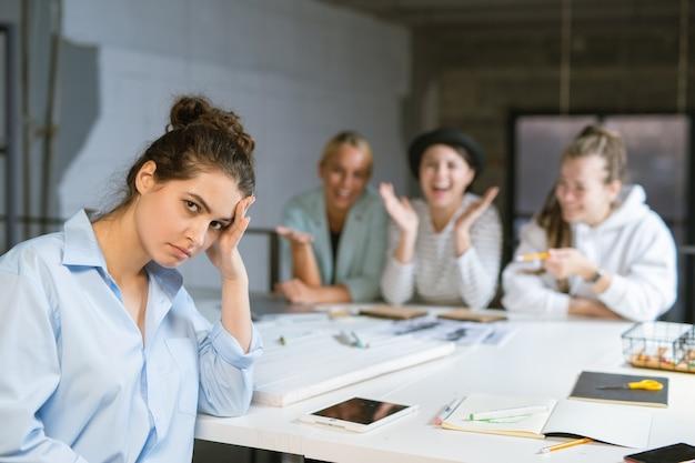 Молодая раздраженная женщина в синей рубашке смотрит на тебя, пока ее друзья на заднем плане стонут на нее
