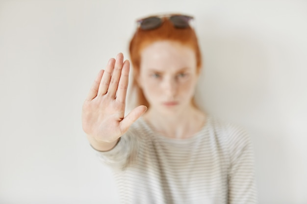 Young annoyed woman with bad attitude making stop gesture with her palm outward, saying no, expressing denial or restriction. negative human emotions, feelings, body language. selective focus on hand