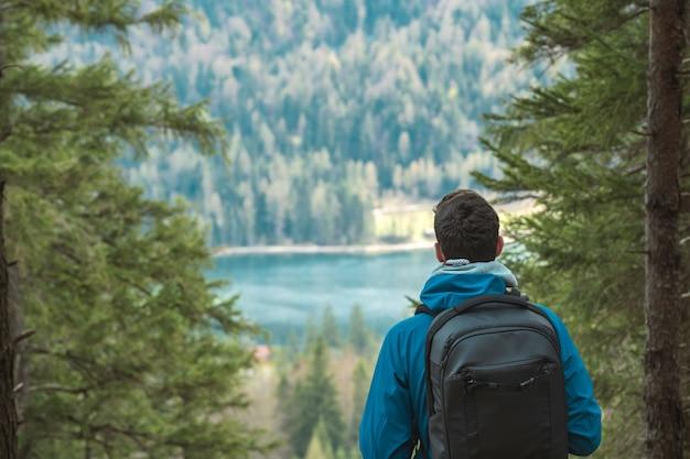 배낭을 가진 젊은 익명의 등산객은 알프스의 산 호수를 본다