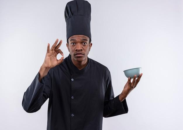 Il giovane cuoco afroamericano ansioso in uniforme del cuoco unico tiene il segno giusto della mano di gesti e della ciotola isolato su fondo bianco con lo spazio della copia