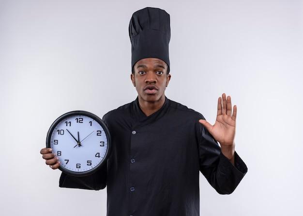 Giovane cuoco afro-americano ansioso in uniforme del cuoco unico tiene il segno della mano di arresto di gesti e dell'orologio isolato su fondo bianco con lo spazio della copia