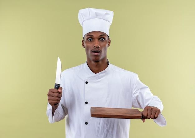 Il giovane cuoco afroamericano ansioso in uniforme dello chef tiene il coltello e lo scrittorio di cucina di legno isolato su fondo verde con lo spazio della copia