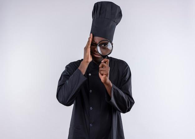 Il giovane cuoco afroamericano ansioso in uniforme del cuoco unico osserva tramite la lente d'ingrandimento o la lente di ingrandimento su bianco con lo spazio della copia