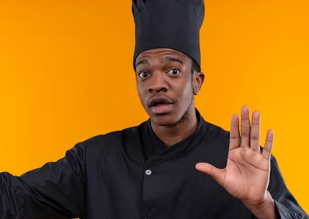 Молодой взволнованный афро-американский повар в униформе шеф-повара жестами останавливает руку, изолированную на оранжевом фоне с копией пространства
