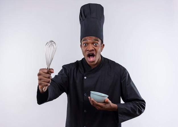Молодой взволнованный афро-американский повар в униформе шеф-повара держит миску и венчик на белом фоне с копией пространства