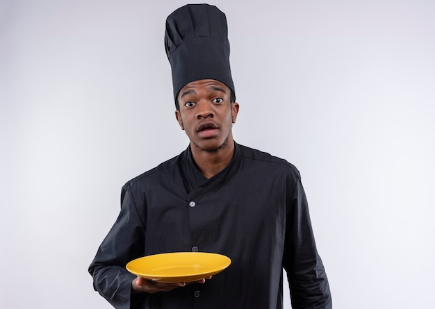 Молодой взволнованный афро-американский повар в униформе шеф-повара держит пустую тарелку на белом фоне с копией пространства