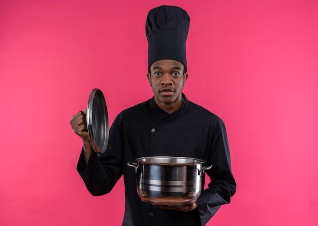 シェフの制服を着た若い気になるアフリカ系アメリカ人の料理人は鍋を保持し、コピースペースでピンクの背景に分離されたカメラを見ます