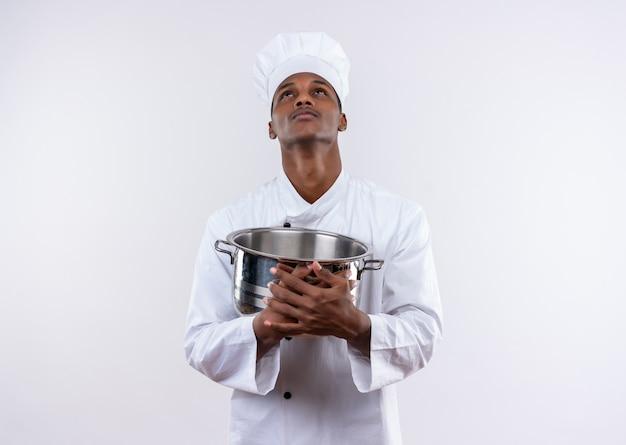 シェフの制服を着た若い気になるアフリカ系アメリカ人の料理人は鍋を保持し、コピースペースで孤立した白い背景を見上げます