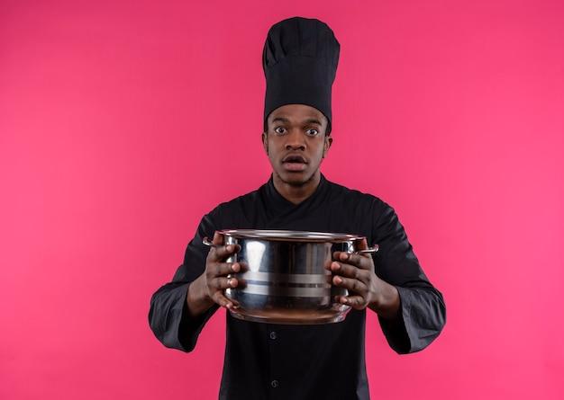 シェフの制服を着た若い気になるアフリカ系アメリカ人の料理人は、コピースペースでピンクの背景に分離された鍋を保持します